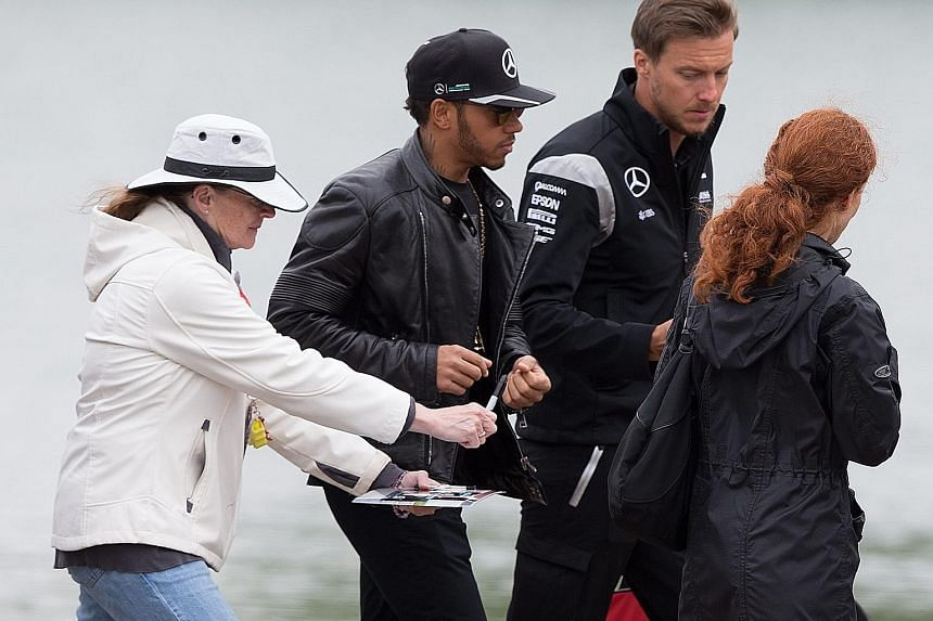 A fan seeking Mercedes Formula One world champion driver Lewis Hamilton's autograph as he arrives at the Gilles Villeneuve circuit in Montreal.