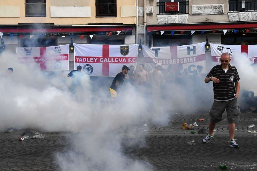 People react to tear gas thrown by French police during a gathering by England supporters in Marseille, on June 10, 2016.