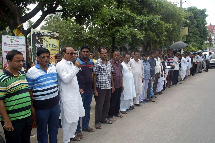Bangladeshi men form a human chain in protest against the killing of Hindu monastery worker Nitya Ranjan Pandey, who was hacked to death in Pabna on June 10, 2016.