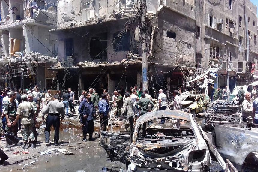 Syrians gathering at the scene of a double bomb attack outside the Sayeda Zeinab shrine, on June 11, 2016.