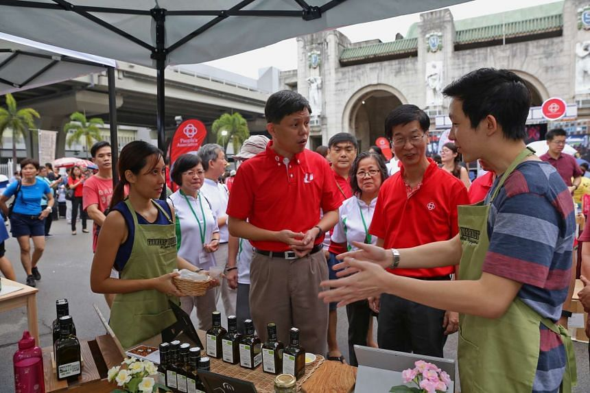 Mr Lance Low (right) and Ms Yuen Ling from local enterprise Farmers Harvest explaining their olive oil products to MP Chan Chun Sing at a carnival at the Tanjong Pagar Railway Station.