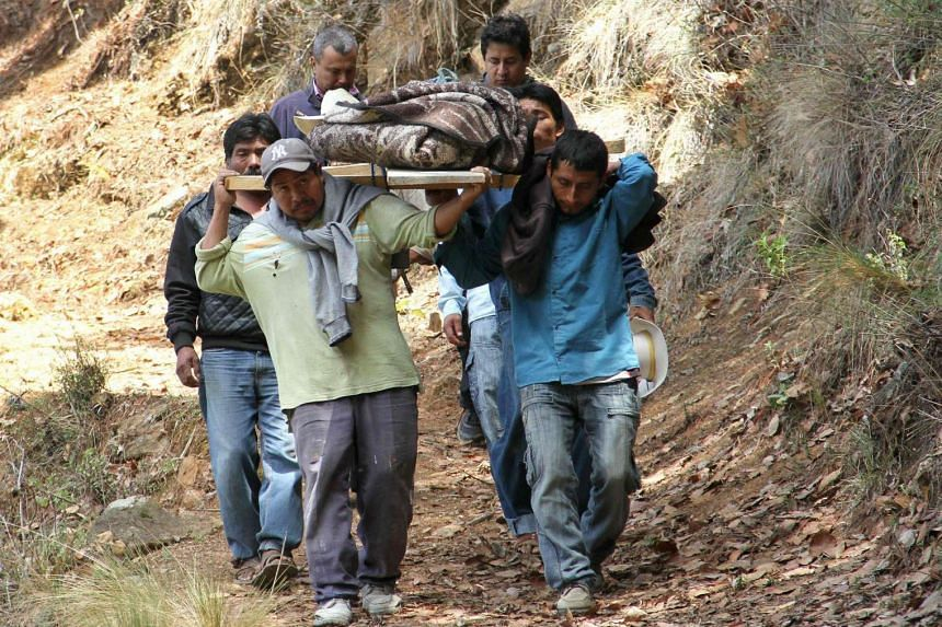 Residents carrying the body of one of the 11 members of a family shot dead at El Mirador, Mexico, on June 10.