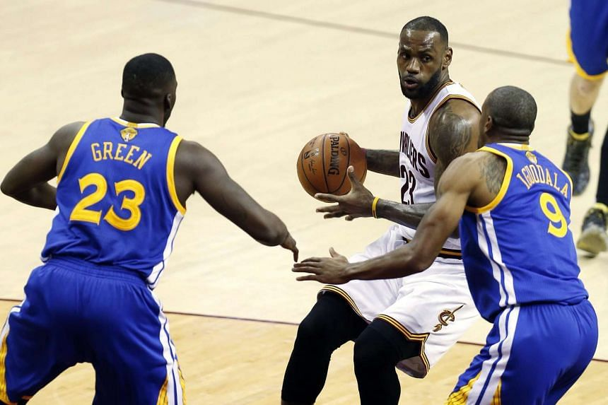 Golden State Warriors forward Draymond Green (left) and forward Andre Iguodala (right) defend against Cleveland Cavaliers forward LeBron James (centre).