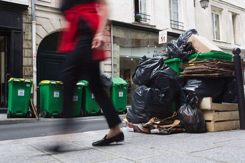 A garbage collectors' strike, made worse by torrential rains, has left stinking piles of rubbish all over Paris.