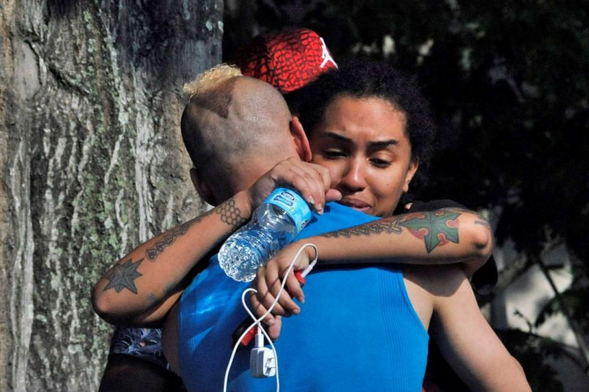 Friends and family members embrace outside the Orlando Police Headquarters during the investigation of a shooting at the Pulse nightclub, where people were killed by a gunman, in Orlando, Florida, on June 12, 2016.
