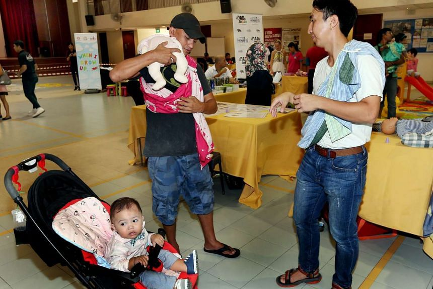 Mr Amir Singh (centre) and Mr Khu Jia Vui (right) practising baby-wearing at the Henderson Community Club while Mr Amir's son Archilles Troy, 11 months, looks on.