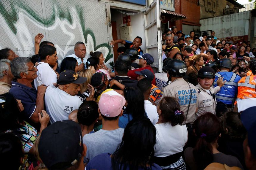 People gathering to try to buy pasta while riot police try to control the crowd outside a supermarket in Caracas, Venezuela, on June 10, 2016.