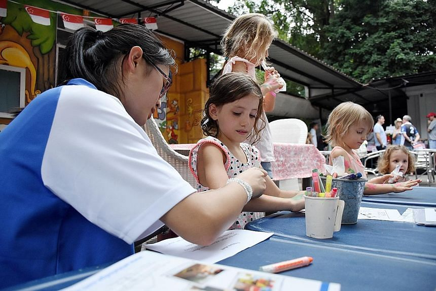 Children getting their arms painted yesterday at the farmers' market in Loewen Road. Melbourne Specialist International School set up a booth there selling cards and bookmarks made by its students to raise funds to build a covered walkway between the