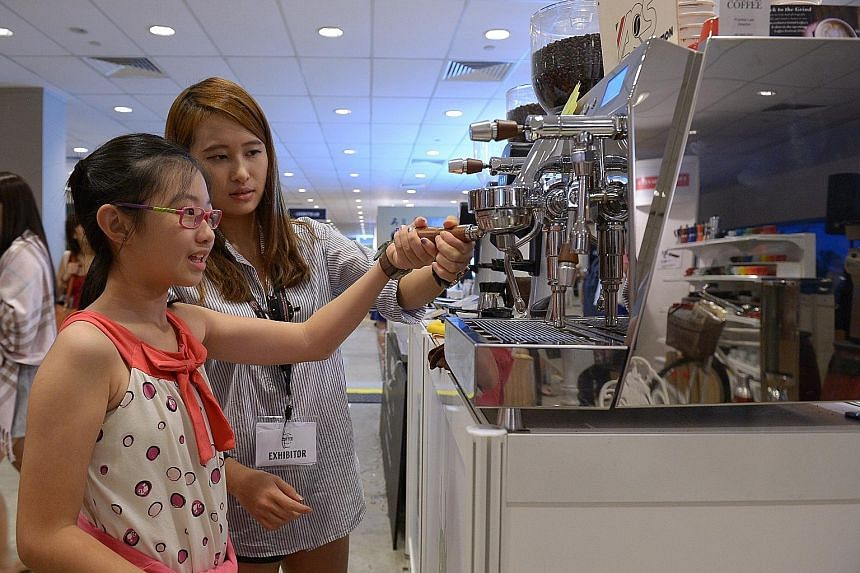 """Ms Yong Han learning to use the """"Vesuvius"""" from Ms Elle Low of Grind Coffee. About 200 people enjoy the free screening of 7 Letters and Eating Air. Specially designed spaces, such as a vintage kopi-tiam, a bean bag corner and an F&B square, are popul"""
