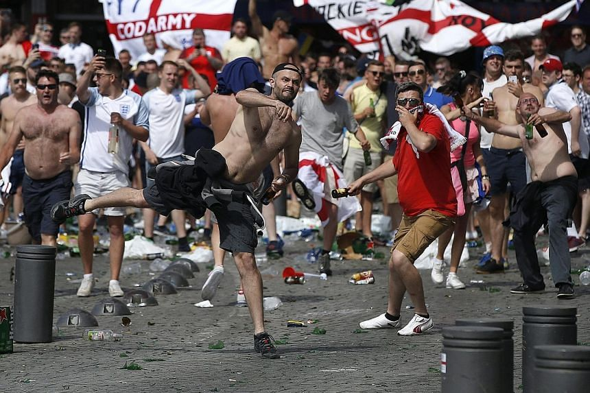 England supporters (above) throwing glass bottles as they clash with French riot police in Marseille yesterday before their country's match against Russia in Euro 2016. An England fan (below) being detained by security personnel.