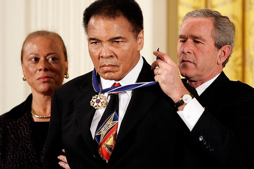 November 2005 US President George W. Bush confers the Presidential Medal of Freedom on Ali as the champ's wife Lonnie watches, during a ceremony at the White House in Washington.