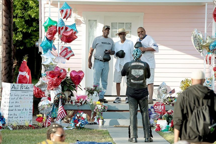 LEFT: A pair of boxing gloves, among other tokens, are placed on a memorial at the Muhammad Ali Center in Kentucky. BELOW: Ali's childhood home in Grand Avenue in Louisville has turned into another memorial. From former US president Mr Clinton (above