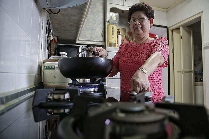 LEFT: Madam Lim, 67, has stopped worrying about being forgetful after getting the new hob last year. ABOVE: The new hob's digital timer can be pre-set to up to 120 minutes. When the time is up, the gas supply is cut off and an alarm alerts the user.