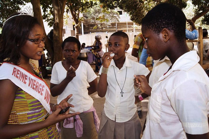 "Togo's ""Universities Virgin Queen"" 2014, Zita Totu (left) gives a talk to school pupils in Lome on February 22."