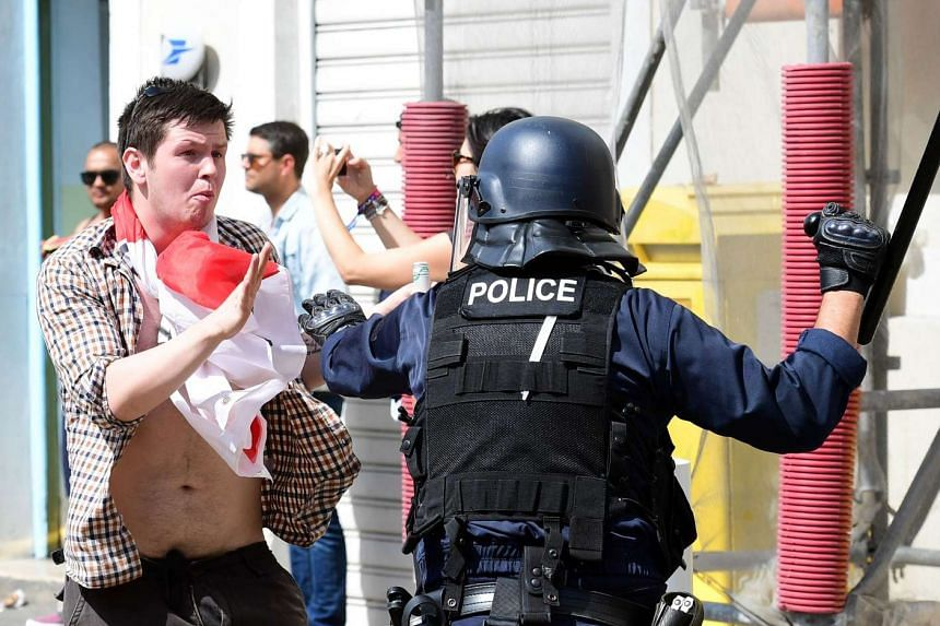 An England fan clashes with police personnel in the city of Marseille, southern France, on June 11, 2016.