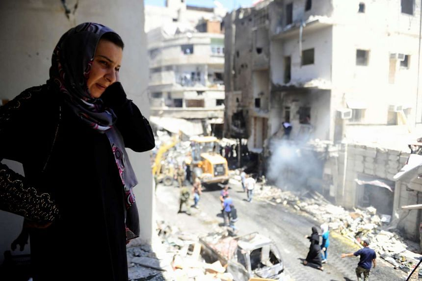 A woman inspects a damaged site after a suicide and car bomb attack in south Damascus Shi'ite suburb of Sayeda Zeinab, Syria June 11, 2016.