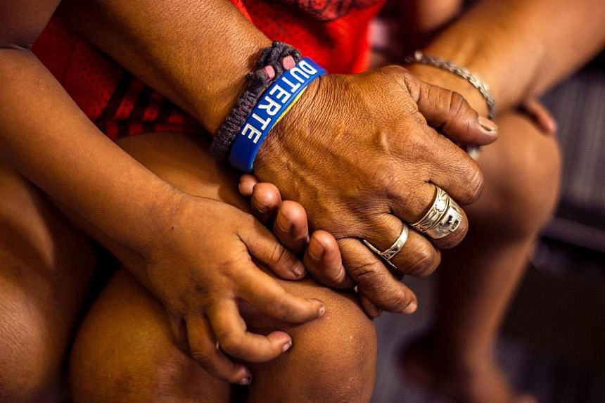 A mother wearing a Duterte wristband, accompanies her minor son at a police station after being temporarily detained for violating a curfer in this picture taken on June 8.