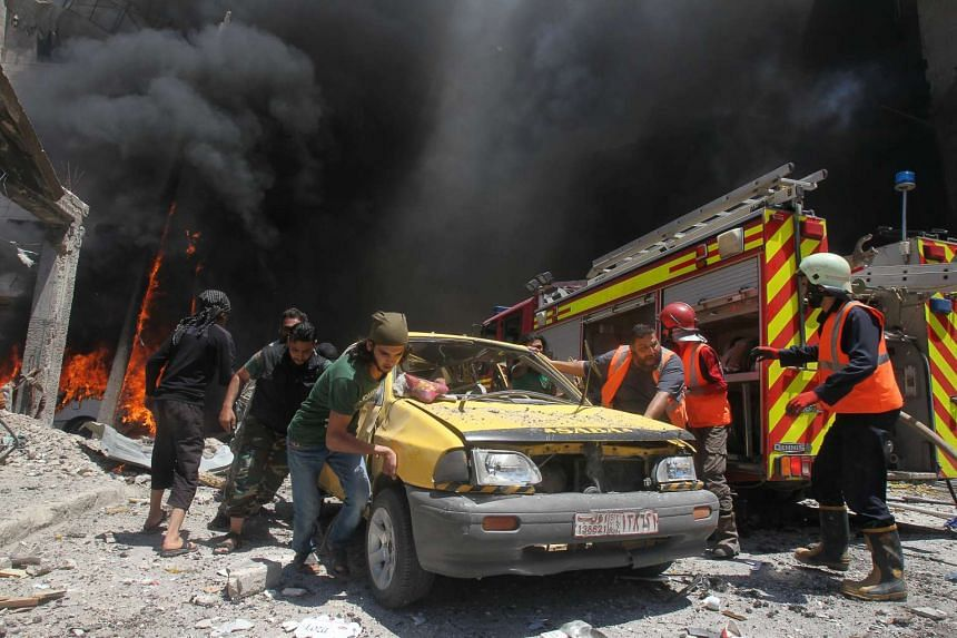 Civil defence officers and rescuers pushing a car away from a site hit by air strikes in Idlib city, Syria, on June 12, 2016.