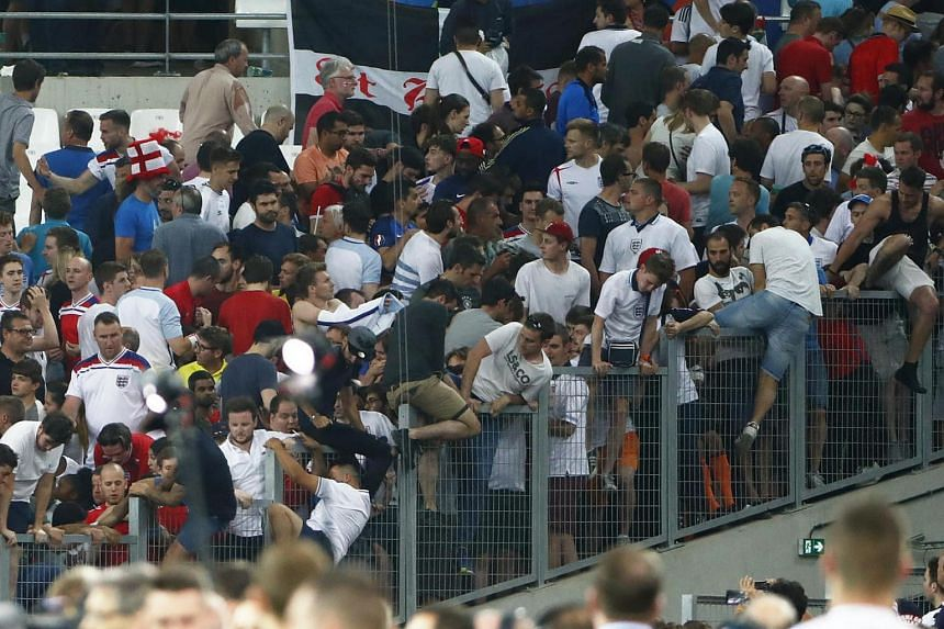 England fans climb over fences as they try to escape trouble in the stadium at full time.