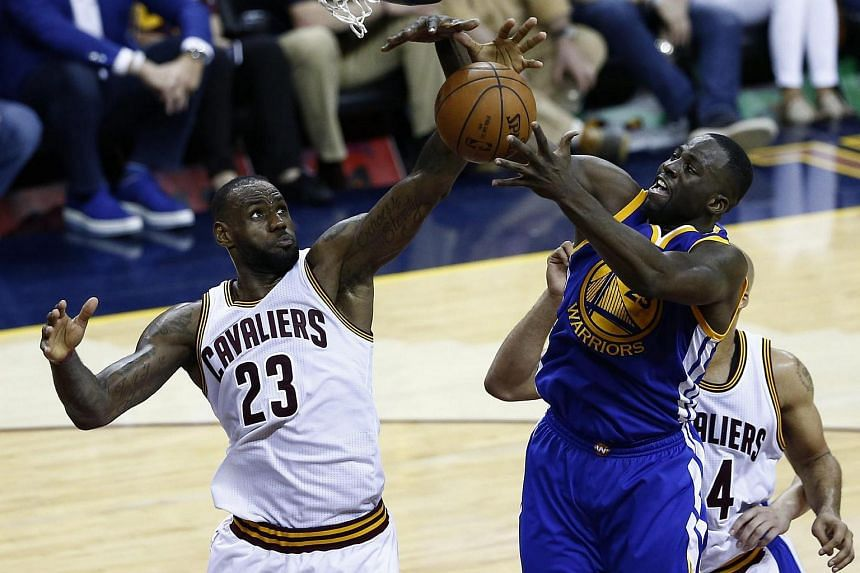 LeBron James (left) goes for a rebound against Golden State Warriors player Draymond Green during the second half of the NBA Finals basketball game four between the Golden State Warriors and the Cleveland Cavaliers.