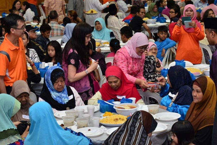 Speaker for Parliament Madam Halimah Yacob distributing cash and vouchers to needy Marsiling residents at a fast-breaking session at Marsiling Community Club on June 12, 2016.