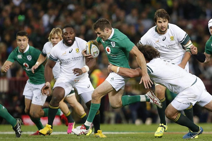 Springbok's Frans Malherbe (right) tackles Ireland's Jared Payne (centre) during the match between Ireland and South Africa at Newlands Stadium on June 11.