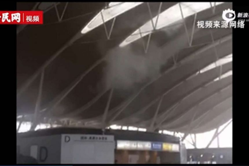"""Smoke is seen from the check-in counter where a """"suspected homemade explosive material"""" exploded at the Shanghai Pudong International Airport."""