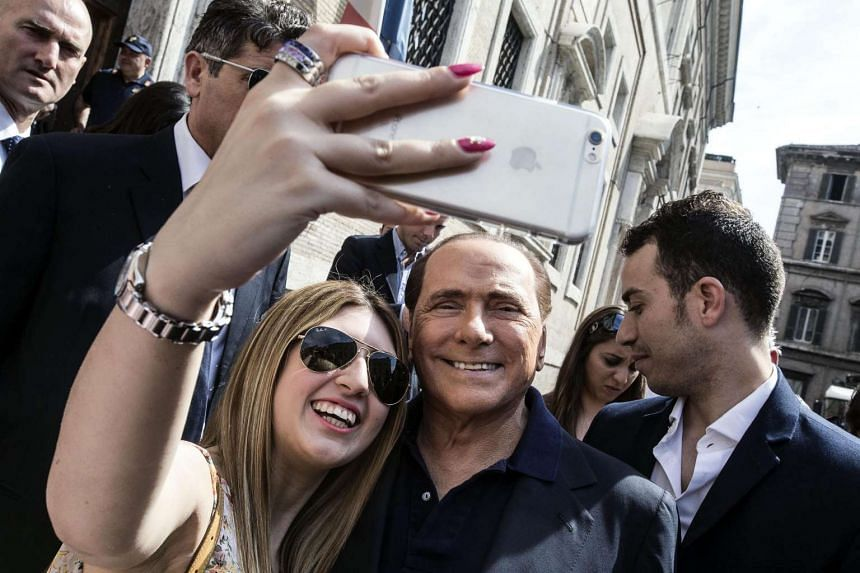 A young woman takes a selfie with Berlusconi outside a polling station in Rome on June 5, 2016.