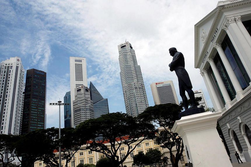 The statue of Sir Stamford Raffles next to the skyline of Singapore.