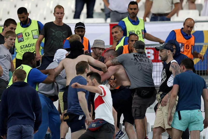 Groups of supporters clash at the end of the Euro 2016 group B football match between England and Russia at the Stade Velodrome in Marseille.