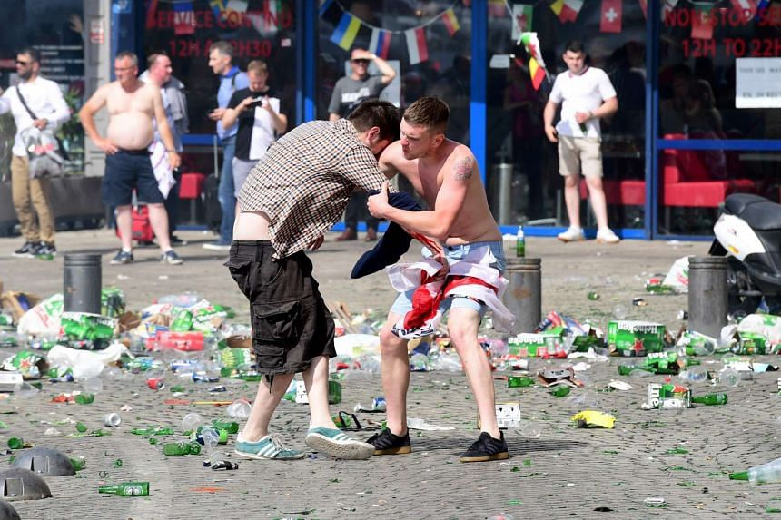 England fans help each other after suffering the effects of tear gas as England fans gather in the city of Marseille, southern France, on June 11, 2016.