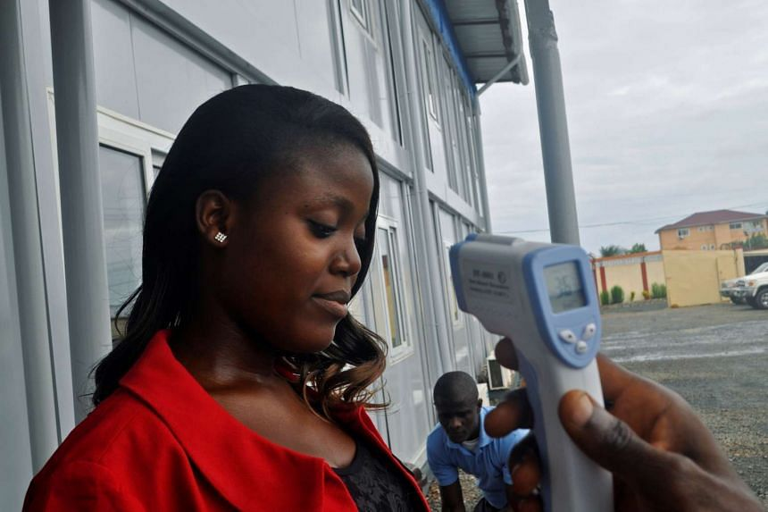 A woman has her temperature checked  on June 9, 2016, before entering the Emergency Operation Centre after the World Health Organisation declared Liberia free of Ebola virus.