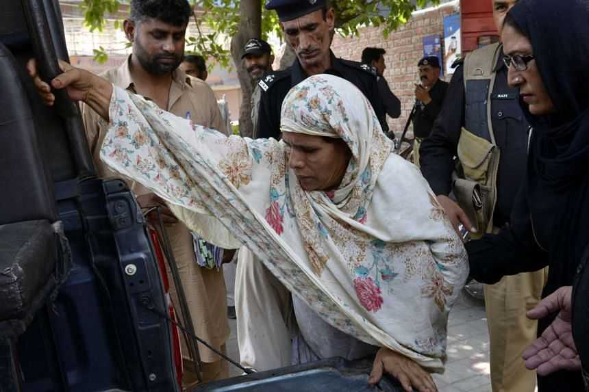 Pakistani police escort Perveen Bibi (centre), who allegedly killed her own daughter by burning her alive, as they go to a local court in Lahore, on June 10, 2016.