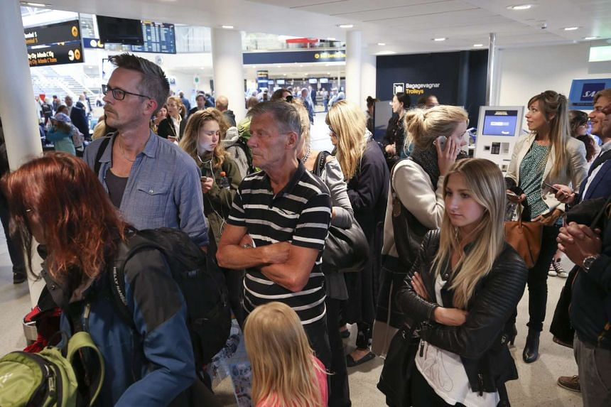 Passengers wait for flight information at Arlanda Airport's domestic terminal in Stockholm, Sweden, on June 10, 2016.