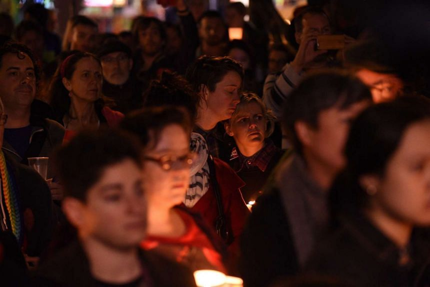 People gather to mourn, honour and remember the victims of the Orlando nightclub shooting at Newtown, in Sydney, Australia, on June 13, 2016.