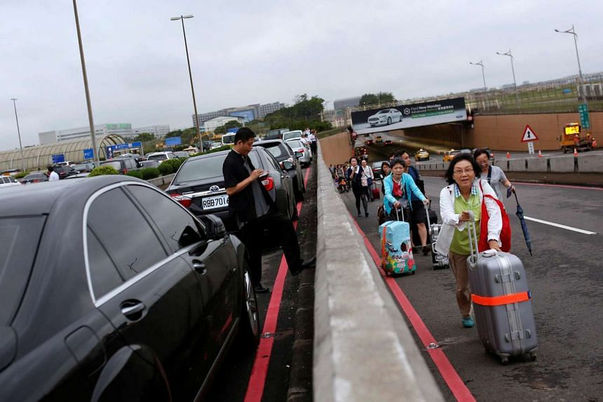Passengers push their luggages past a traffic jam after heavy rains caused flooding at Taoyuan International Airport, on June 2, 2016.