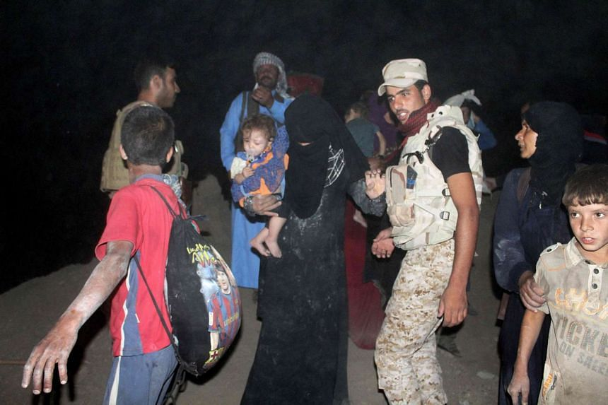 Displaced Iraqi women and their children, fleeing the embattled city of Fallujah, are welcomed by Iraqi pro-governement forces upon their arrival in an area that they control, late at night on June 10, 2016 in Amriyat al-Fallujah, some 30 kilometers
