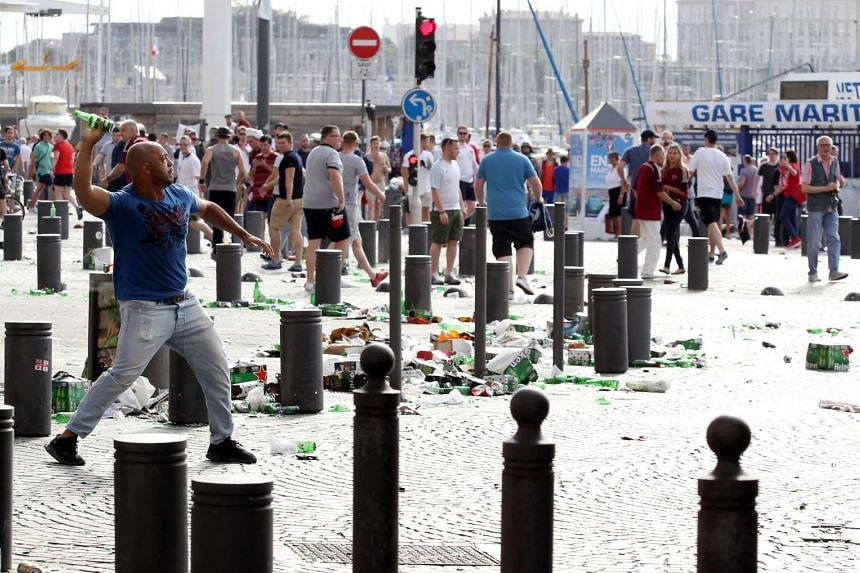 A man throws a beer can during street brawls ahead of the Euro 2016 football match England vs Russia, southern France, on June 11, 2016.