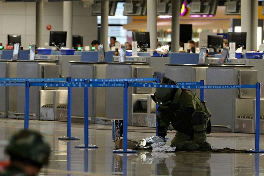 A paramilitary bomb disposal expert inspects a luggage left near a check-in counter after an explosion at Pudong Airport in Shanghai, on June 12, 2016.