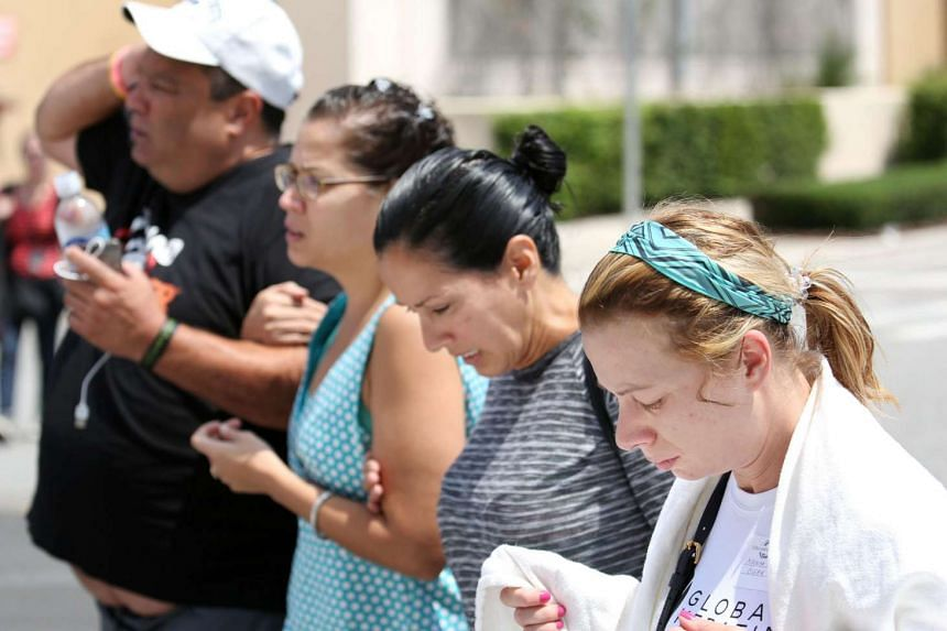 People arrive at a hotel where family members gather in the aftermath of a mass shooting in Orlando, Florida, on June 12, 2016.
