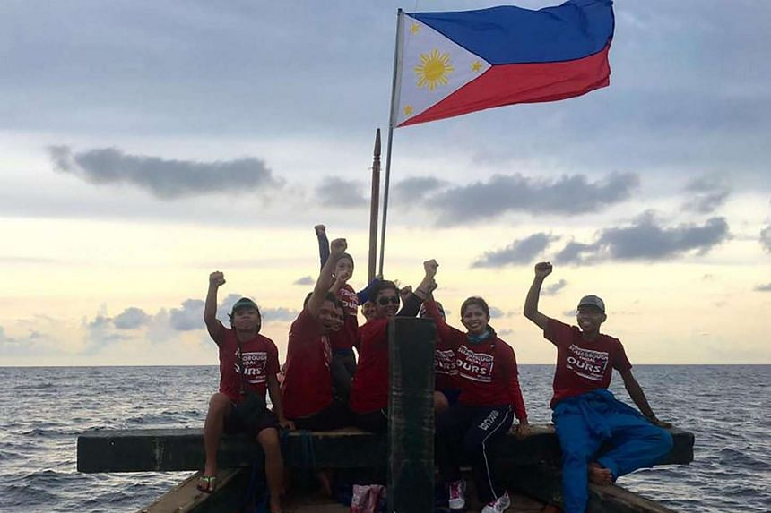 Members of the group Kalayaan Atin Ito (Freedom This Is Ours) raise their fists next to the Philippines flag as they sail to Scarborough Shoal to protest China's occupation of the marine feature.