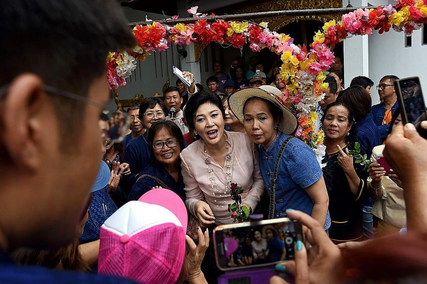 Ms Yingluck posing for pictures with supporters during a visit to a temple in Phrae province, where she was mobbed by photo-taking fans.
