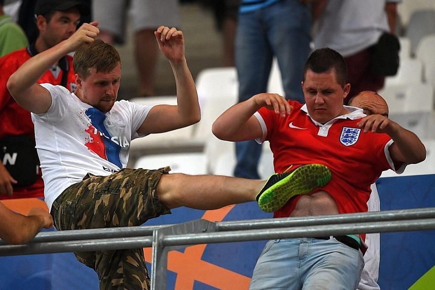 Above: A Russia fan clashing with an England supporter (right) in the stands, as their teams did battle on the pitch.