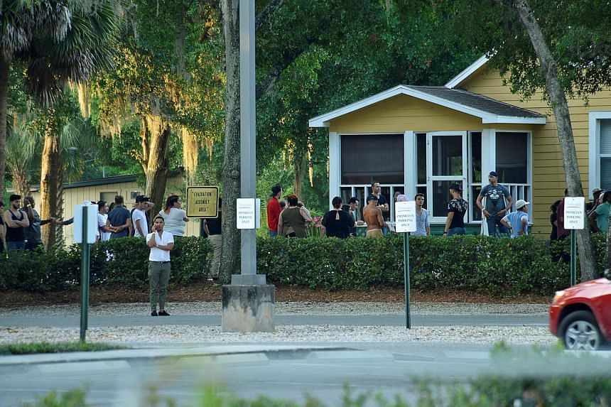 A crowd near the club where police were questioning people. Some had rushed to the club after getting calls from people trapped inside. (Above and left) Friends and family members outside the Orlando Police headquarters yesterday. Officers arriving a