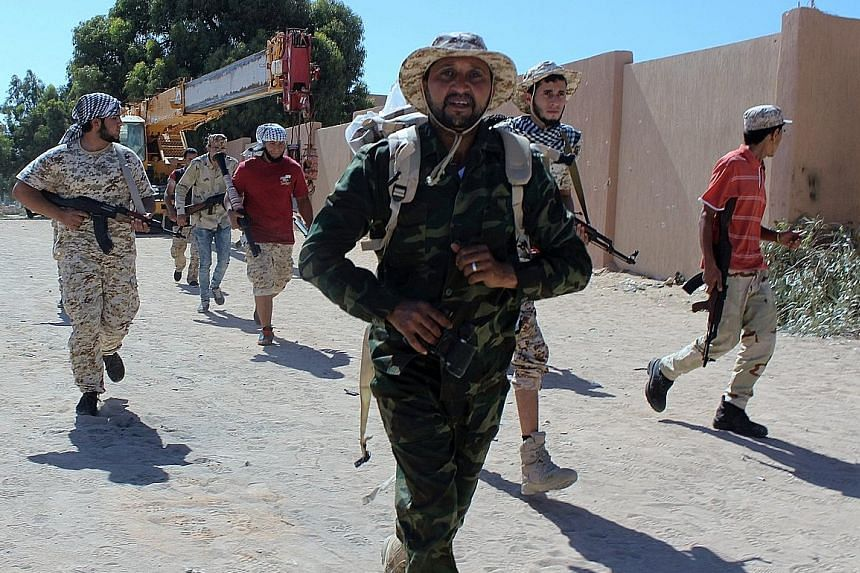 Fighters from forces allied with Libya's new unity government clearing an area in Zaafran, Sirte, on Saturday. The forces entered Sirte on Wednesday and have been advancing more quickly than expected against ISIS.