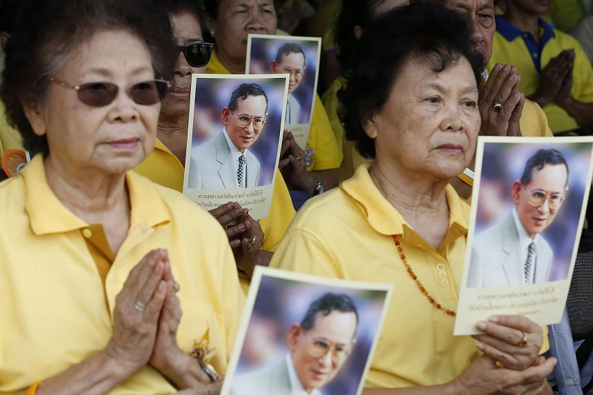 Thai people hold pictures of Thai King Bhumibol Adulyadej as they pray during the celebrations of the monarch's 70th anniversary of accession to the throne on June 9, 2016.