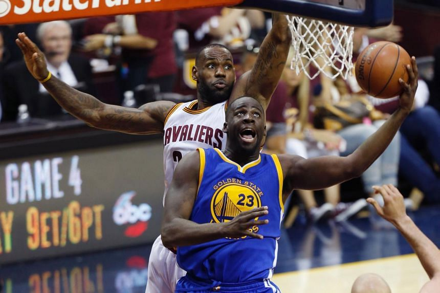 Golden State Warriors forward Draymond Green (right) shoots the ball in front of Cleveland Cavaliers forward LeBron James during Game 3 of the NBA Finals.