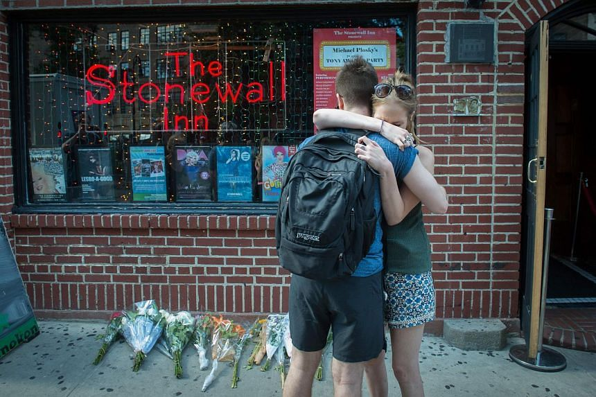 People hug outside the Stonewall Inn near a vigil for the victims in New York on June 12 following the mass shooting at a gay nightclub in Orlando, Florida.
