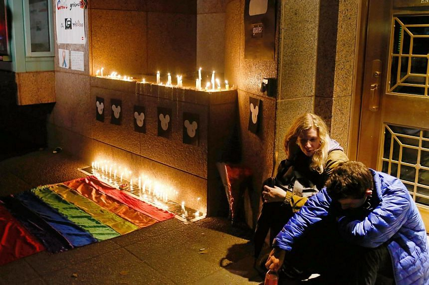 Sitting next to candles and a rainbow flag, people participate in a vigil for victims of a mass shooting at a gay nightclub in Orlando outside of the US Embassy in Santiago, Chile, on June 12.