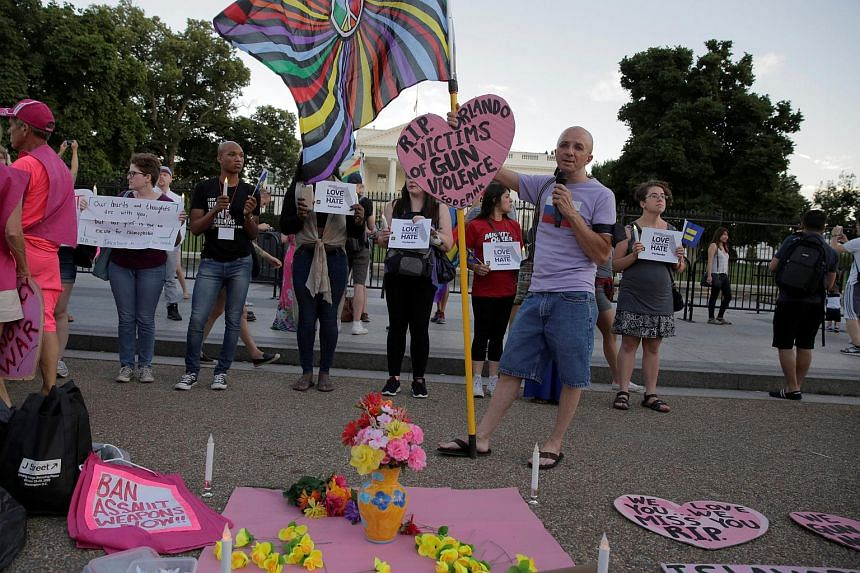 People hold a vigil after the worst mass shooting in US history at a gay nightclub in Orlando in front of the White House in Washington on June 12.